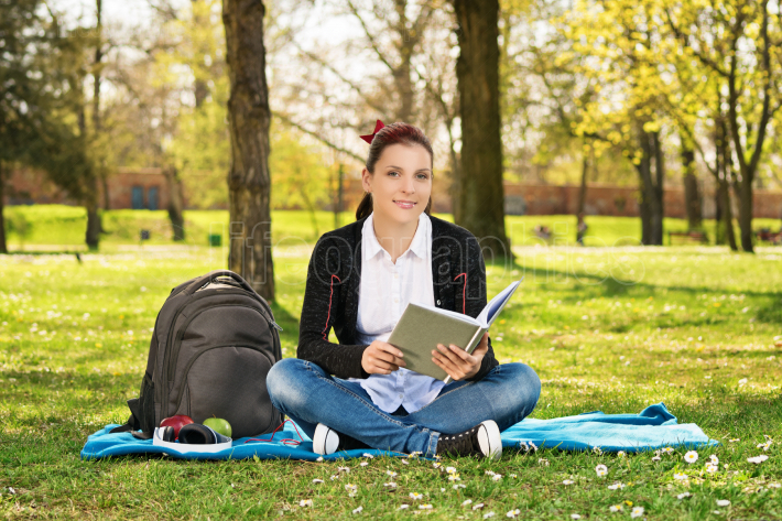 Portrait of a female student in a park holding a book