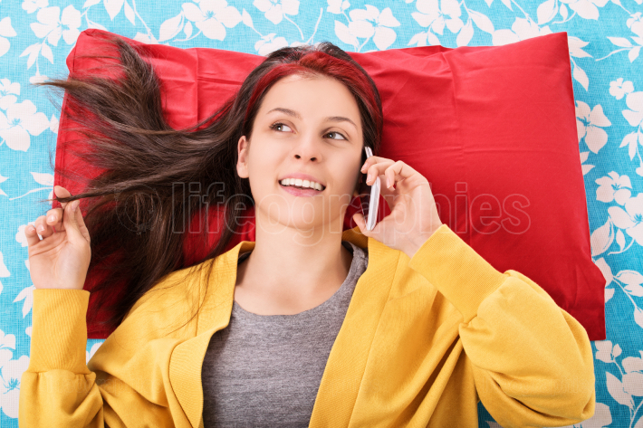 Portrait of a girl in her bed talking on the phone