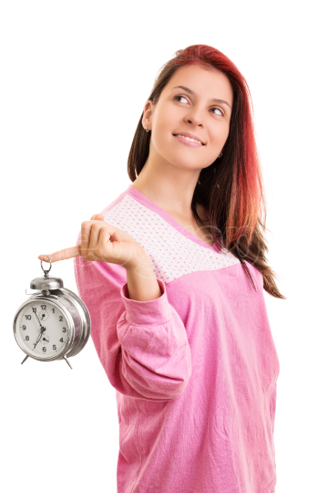 Portrait of a girl in pajamas holding an alarm clock