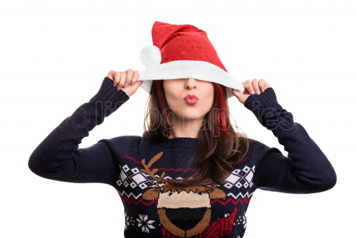 Portrait of a girl putting on Santa's hat over her eyes