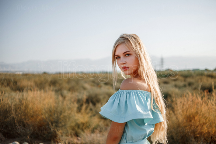 Portrait of a young beautiful caucasian blonde girl in a light b