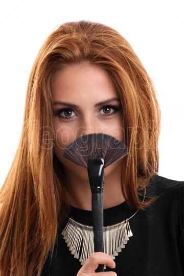 Portrait of a young beautiful girl holding a make up brush