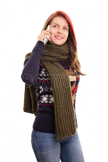 Portrait of a young girl in winter clothes talking on a phone