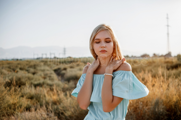 Portrait of young beautiful caucasian blonde girl in light blue