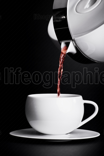 Pouring tea on black background