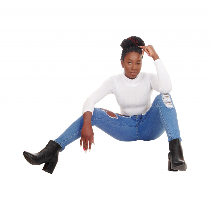 Pretty African female sitting on the floor in jeans