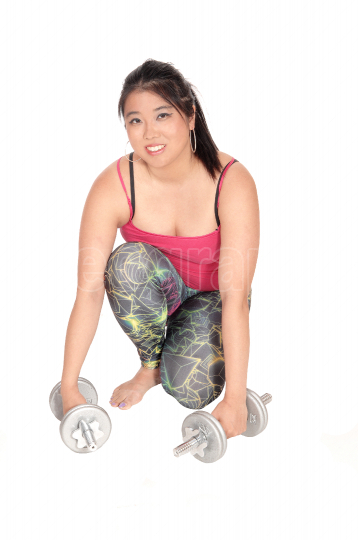 Pretty Asian woman kneeling with two dumbbells
