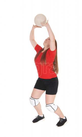 Pretty teenage girl playing volley ball