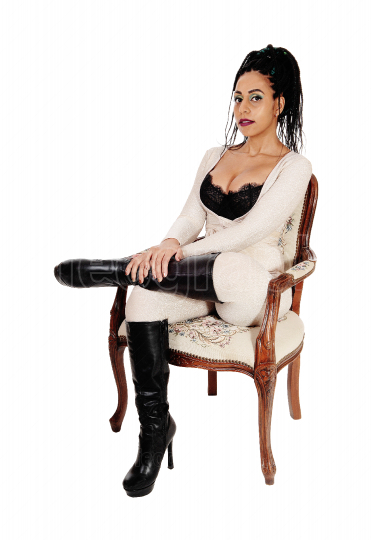 Pretty woman sitting in armchair with her legs crossed
