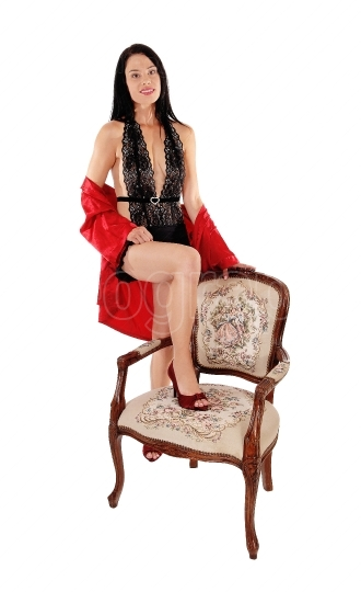 Pretty woman standing in lingerie with old chair