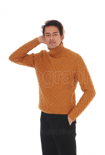 Pretty young man standing in a sweater in the studio