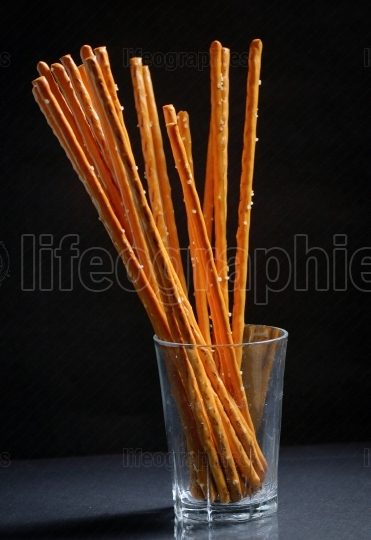 Pretzel sticks in small glass on black background