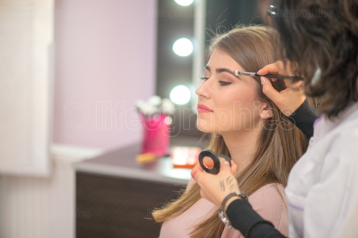 Professional make up artist preparing model for studio shot