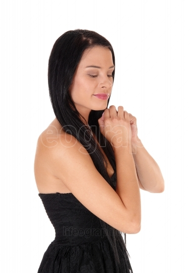 Profile of young woman praying with hands folded
