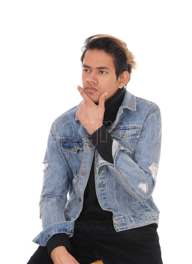 Puzzled young man sitting on a chair in a jeans jacket thinking