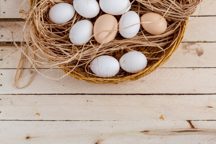 Raw eggs in the hay on a wooden background