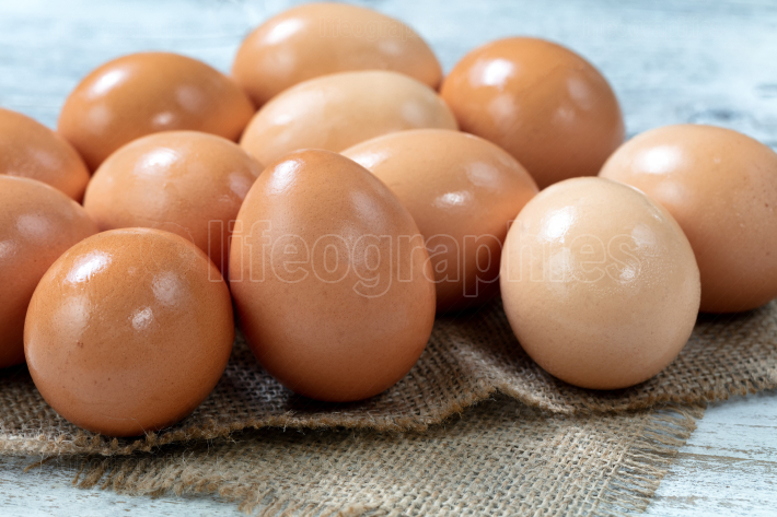 Raw organic brown farm raised eggs on burlap cloth