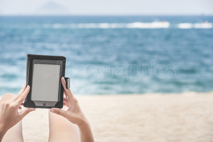 Reading from e-reader on the beach