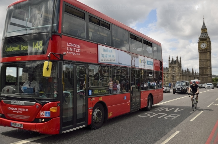 Red bus and bicyclist in motion and Big Ben, the Palace of Westminster