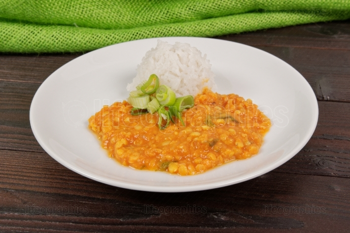 Red lentil in a sauce and rice on a table