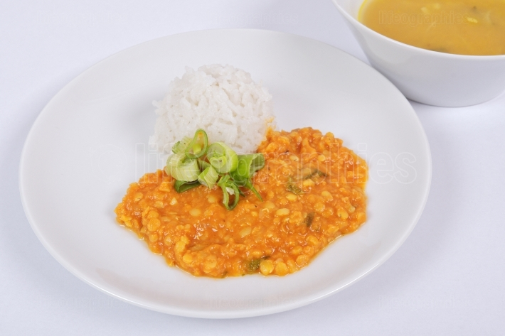 Red lentil in a sauce ansd rice on a white