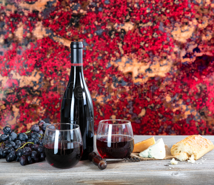 Red wine with fresh cheese and baked bread on rustic wooden tabl