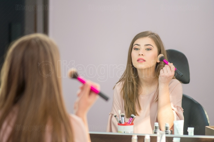 Reflection of young beautiful woman applying her make up, looking in a mirror