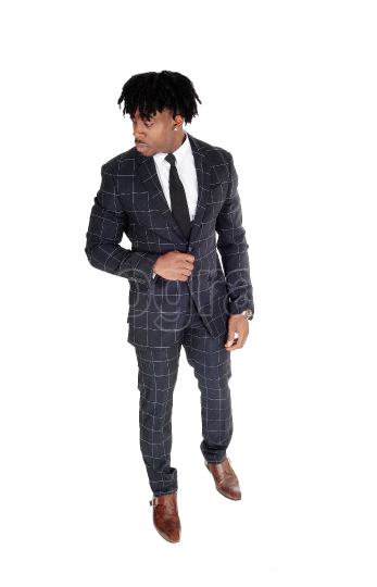 Relaxed black man standing in a dank suit looking away