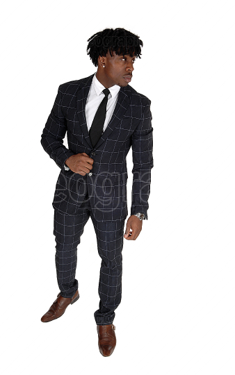 Relaxed black man standing in a suit looking away
