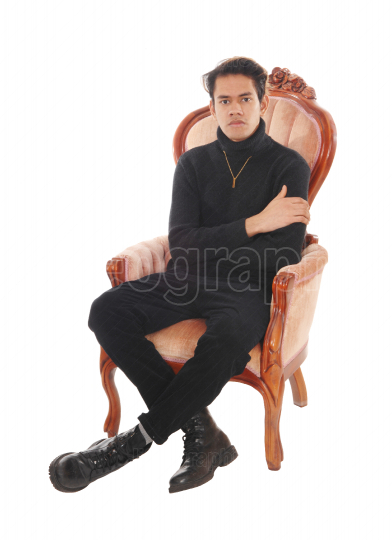 Relaxed young man sitting in a old armchair
