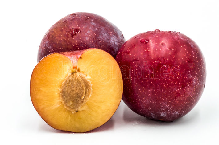 Ripe red round plums and a quarter isolated