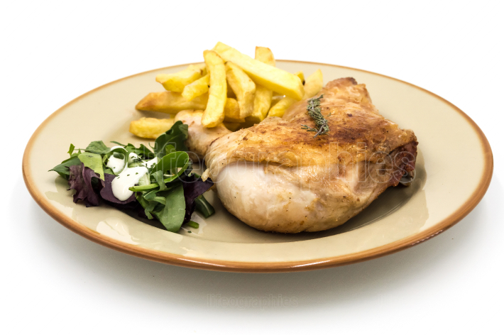 Roasted chicken leg with fries and vegetables