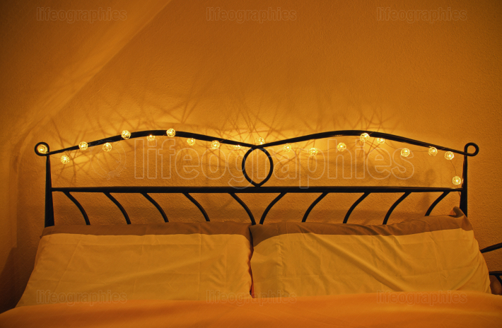 Romantic cozy bed with garland of lights around headboard