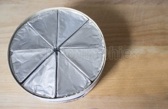 Round cardboard box with melted cheese in aluminium foil on wood
