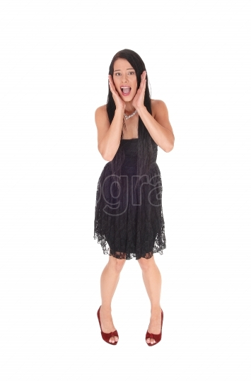 Scared woman standing in black dress hands on face