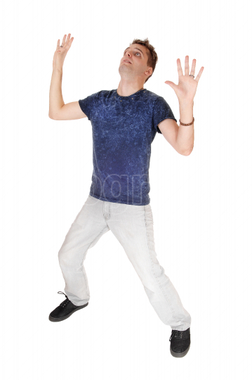 Scared young man with his hands up in the air