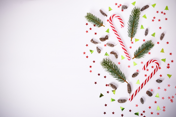 Seasonal composition with fir branches, candy cane and confetti