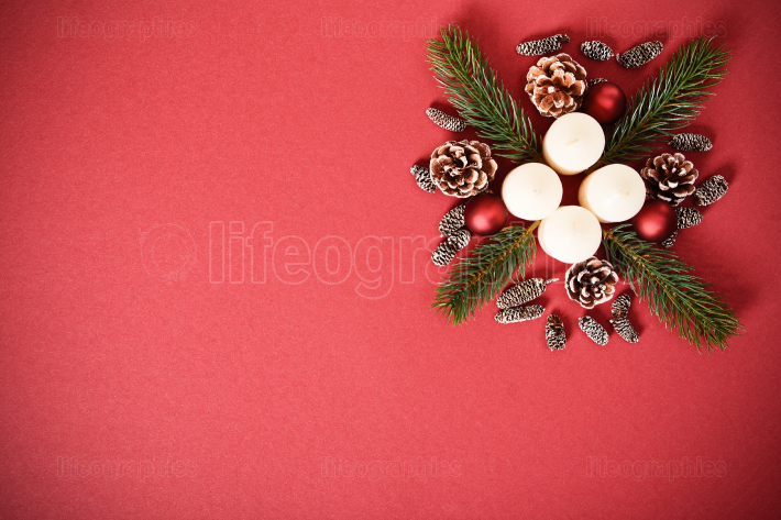 Seasonal greeting card concept with candles, pinecones and everg