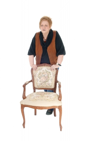 Senior woman standing on armchair