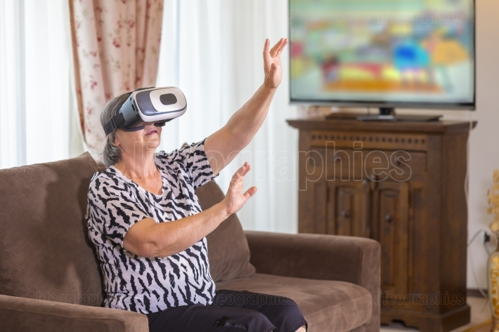 Senior woman with virtual headset or 3d glasses playing