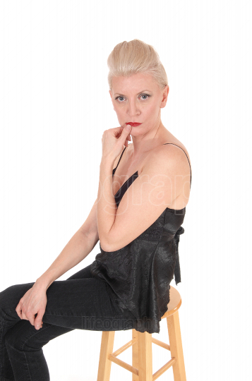 Serious looking blond woman sitting on chair