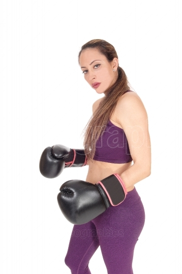 Serious looking woman with black boxing cloves