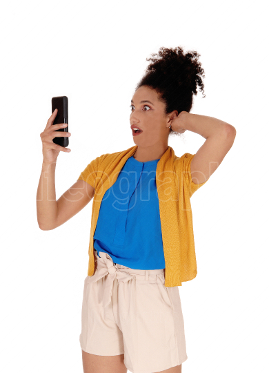 Shocked multi racial woman looking at her cell phone