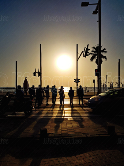 Silhouettes crossing street at sunset