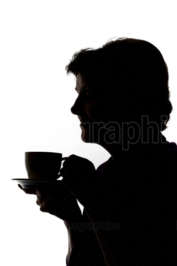Silhouettes of woman drinking coffee