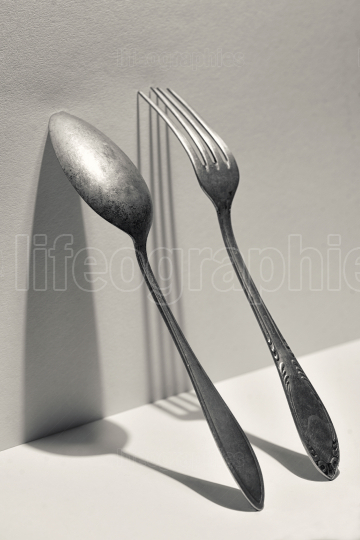 Silver fork and spoon on wall