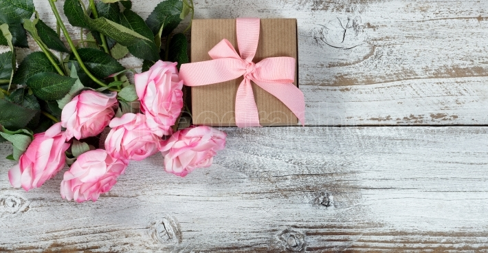 Six pink roses and gift on rustic white wooden background
