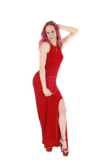 Slim woman standing in a red evening dress from the front
