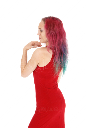 Slim woman standing in profile in a red dress