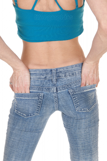 Slim young woman standing from back in jeans, body part
